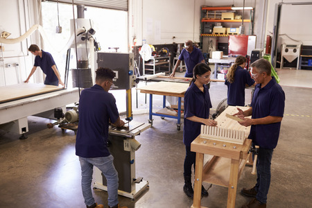 Carpenters Working On Machines In Busy Woodworking Workshop Stock fotó