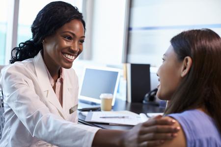 El uso médico de bata blanca Reunión con el paciente femenino