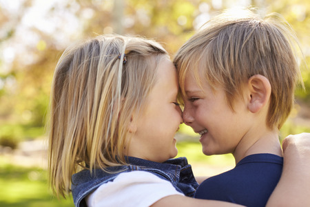 arms around: Young brother and sister nose to nose in a park, side view Stock Photo