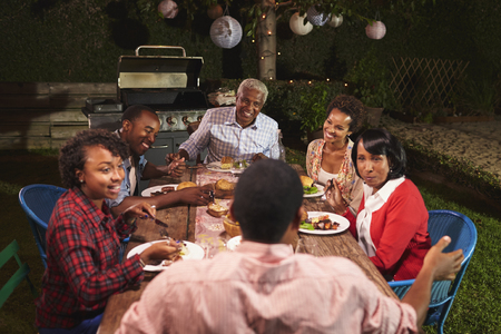 Adult black family talking at dinner in their garden Stock Photo