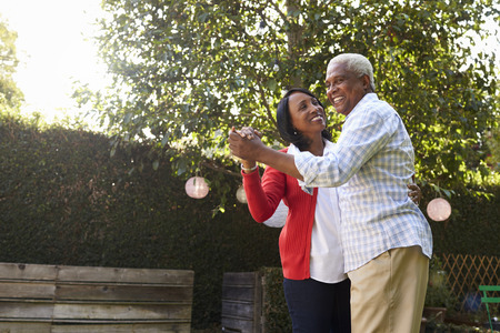 Senior black couple dancing in their back garden