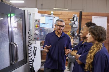 CNC マシン上のエンジニア訓練の実習生 写真素材