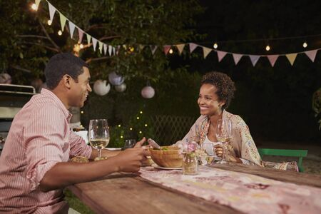 Young African American couple at a dinner table in garden