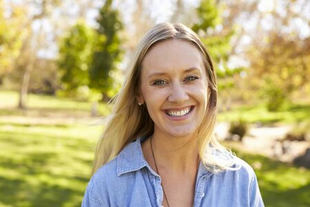 mid thirties: Mid thirties white woman smiling to camera in a park