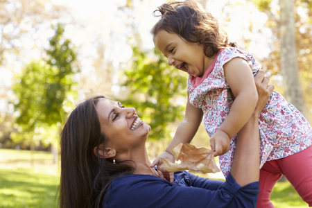 Asian mixed race mum and young daughter playing in park Stock Photo