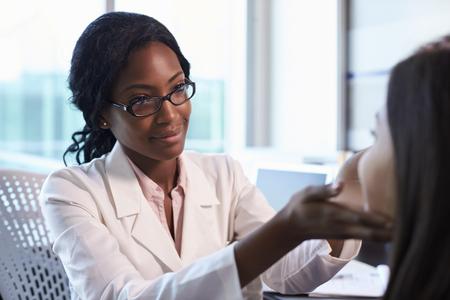사무실에서 흰색 여성 코트를 검사하는 흰 코트에있는 의사 스톡 콘텐츠