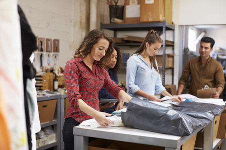 Team in een postkamer verpakking kleding orders voor distributie Stockfoto