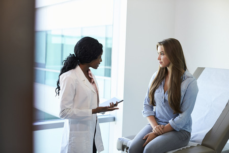 Female Doctor Meeting With Teenage Patient In Exam Room Stock Photo