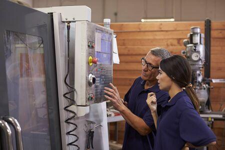 Engineer Training Female Apprentice On CNC Machine