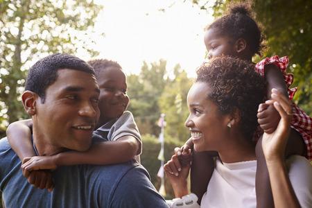 Afro-Amerikaanse ouders geven kinderen piggyback ritten