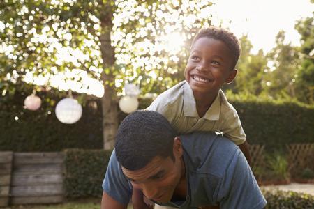 Jonge zwarte jongen die op zijn vader speelt is terug in een tuin