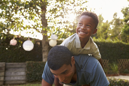 Junger schwarzer Junge, der zurück auf seinem Vati in einem Garten spielt Standard-Bild - 71352917
