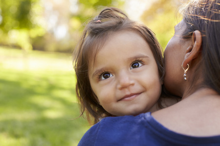 Mixed race mother holding her daughter, over shoulder view Stock Photo