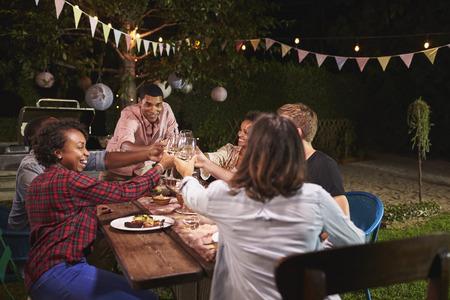Vrienden en familie maken een toast bij het dinerfeest in de tuin