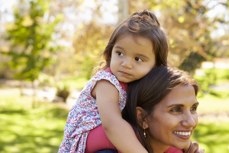 Mixed race mother carrying young daughter on her shoulders Stock Photo