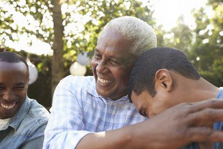 De hogere mens die zijn twee volwassen zonen in tuin begroeten, sluit omhoog Stockfoto