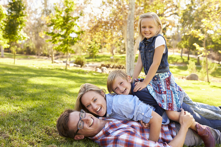 Family piled on top of each other in a park look to camera Stock Photo