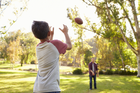 Dad and son throwing American football to each other in park 免版税图像