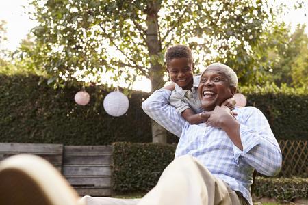정원에 앉아 할아버지를 수용하는 젊은 흑인 소년