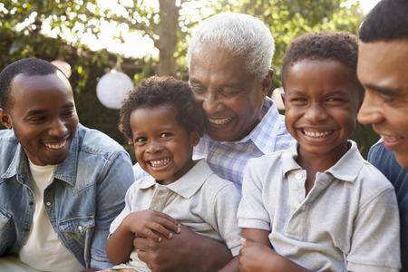 Multi generatie mannelijke familieleden verzamelden zich in een tuin