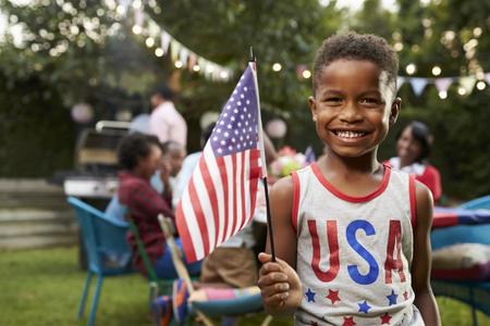 Jonge zwarte jongen die de vlag op 4 juli familie tuinfeest