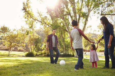 Junge Mischrassefamilie, die mit Ball in einem Park, hintergrundbeleuchtet spielt