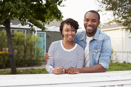 pareja en casa: African American couple look to camera outside their house