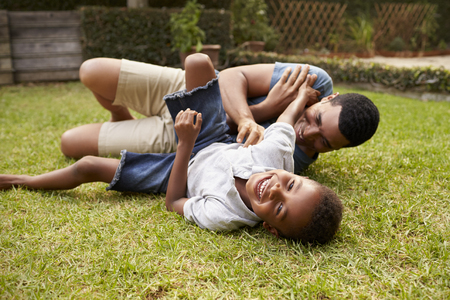 tickling: Black father and young son play lying on grass, low angle Stock Photo