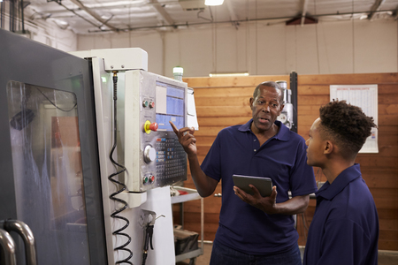 Engineer Training Young Male Apprentice On CNC Machine