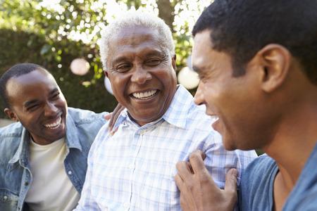 Senior man praten met zijn volwassen zonen in de tuin, close-up