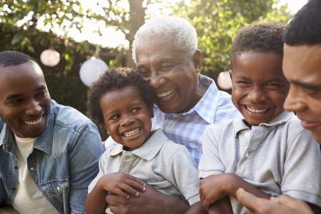 Multi generatie mannelijke familieleden verzamelden zich in een tuin Stockfoto - 71353051