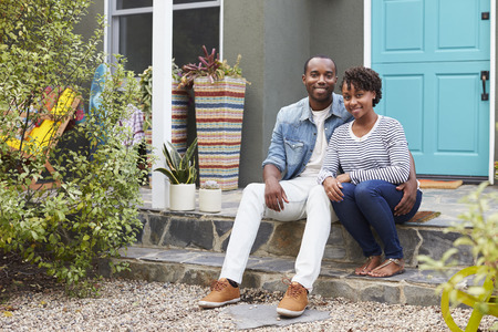 Young couple sit looking to camera outside their new house