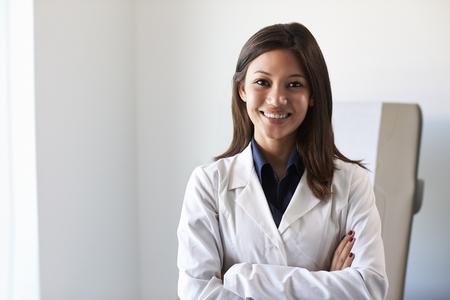 bata blanca: Retrato del doctor de sexo femenino uso de abrigo de cuarto de exámenes En Blanco