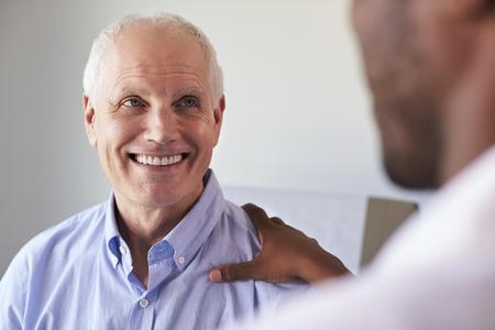 Reunión del doctor con el paciente masculino maduro en la sala de examen Foto de archivo - 71353078