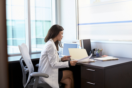 bata blanca: Female Doctor Wearing White Coat Reading Notes In Office