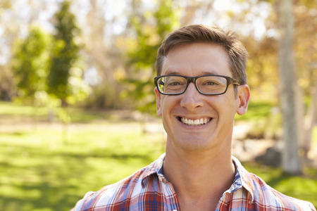Middle aged white man in glasses smiling to camera in a park Stock Photo