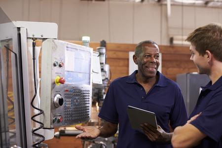 Ingeniero máquina de entrenamiento Hombre aprendiz En CNC