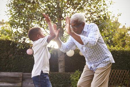 niños negros: Negro abuelo jugando con su nieto en un jardín