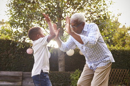 Black grandfather playing with his grandson in a garden