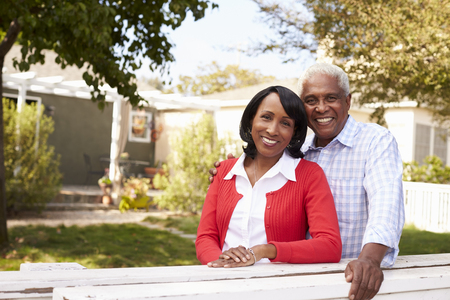 Senior black couple look to camera outside their new house Imagens