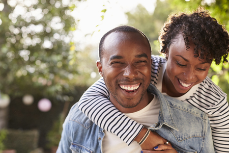 Laughing young black couple piggyback in garden, to camera Stock fotó