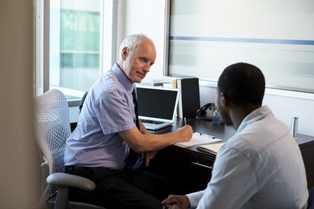 Arts in overleg met mannelijke patiënt in het kantoor