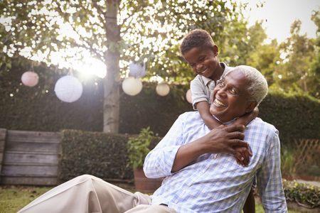 Young black boy embracing grandfather sitting in garden Фото со стока