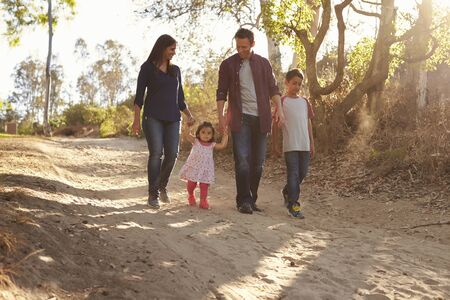 tranquility: Mixed race family walking on rural path, front view Stock Photo