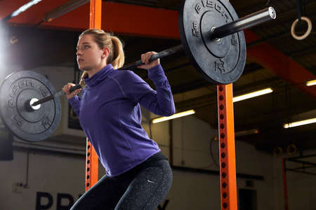Donna In Gym Lifting Pesi Sul Barbell