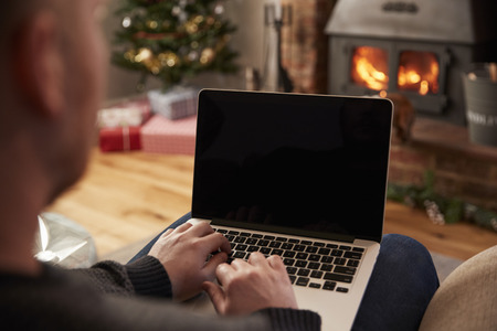 Man Using Laptop In Room Decorated For Christmas Фото со стока