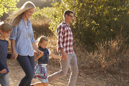 Young white family walking on a path in sunlight, side view photo