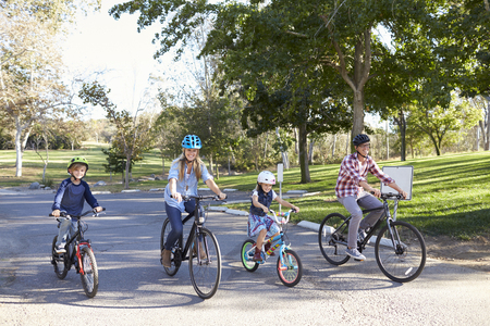Young white family cycling together through a park photo