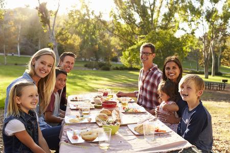 カメラをテーブルにピクニックを持つ 2 つの家族