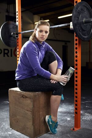keeping fit: Portrait Of Young Woman In Gym Lifting Weights On Barbell Stock Photo